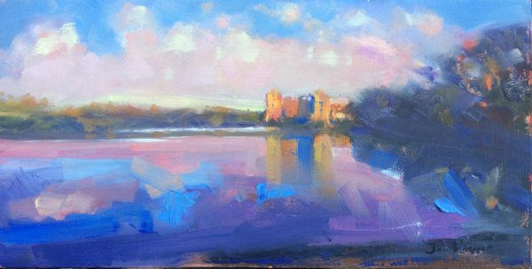 Late Evening Light at Carew Castle with a blue colourful mill pond and castle glowing orange with the Sunlight